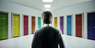 Man standing in hallway with multicolored doors --- Image by © CJ Burton/Corbis